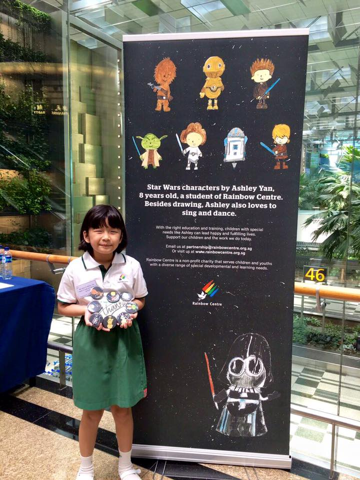 Ashley at Changi Airport X-Wing exhibit where the pins were sold to raise funds.